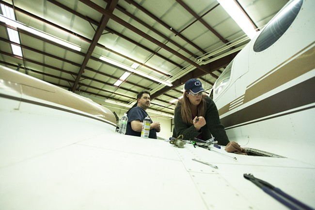 Second year student Monica Miller, right, removes a starter relay from a Cessna 421 as fellow student Brian Helm watches - YOUNG KWAK