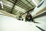 Second year student Monica Miller, right, removes a starter relay from a Cessna 421 as fellow student Brian Helm watches.