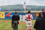 Seth Spivev (11), left, respects the American flag as the National Anthem is played at Avista Stadium.