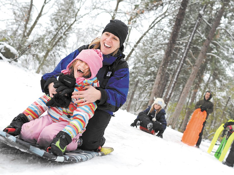 Shelli Montilla and her daughter, Emma, sled at Manito Park on Monday. - CHRISTIAN WILSON