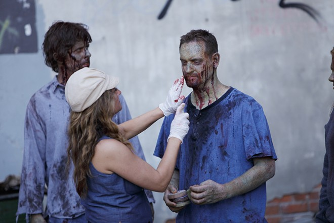 Special Effects and Makeup Artist Heather Dupree, center, touches up makeup on zombie extra Josh Depue, right, as James Gallina looks on. - GAL