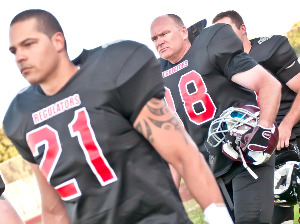 Spokane County Sheriff Ozzie Knezovich (middle) marches onto the football field - AMY HUNTER
