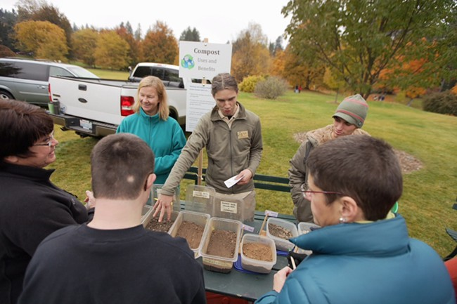Spokane Master Composters volunteer Ryan Herring, center, speaks about soil with Sandie Potts, right. - YOUNG KWAK