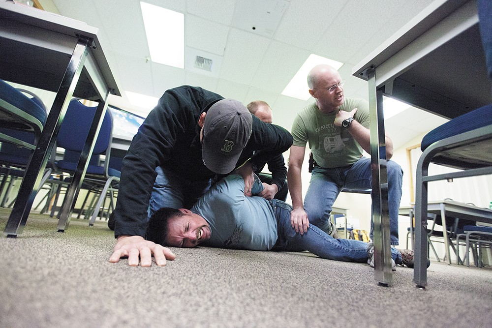 Spokane Police Officers Maurio Jaurez, left, Brad Moon, center, and Greg Ronan, right, subdue fellow Officer Ron Tilley, playing the role of a psychotic subject with excited delirium during Crisis Intervention Training. - YOUNG KWAK