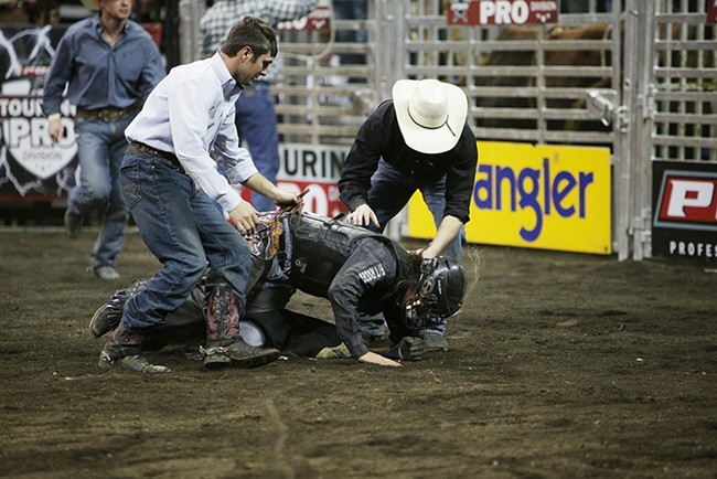 Stetson Lawrence, center, of Williston, N.D., is slow to get up after being attacked by 973 Tornado Alley, not pictured, after falling off during Flight 1. He rode 7.41 seconds before falling off the bull. - YOUNG KWAK