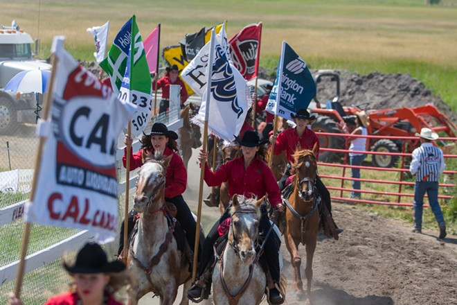 The Cheney Rodeo Flag Team rides into the BiMart Arena with the flags of the companies who have sponsored the Rodeo. - MATT WEIGAND