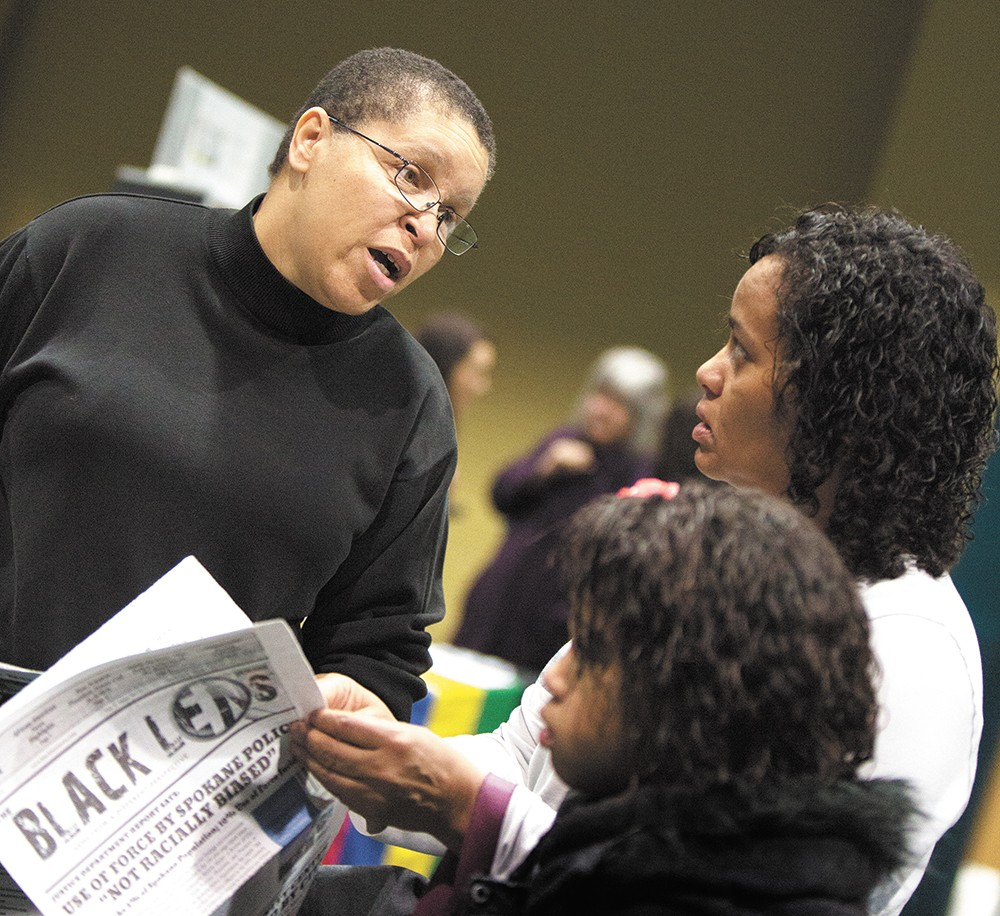 The editor and publisher of the Black Lens, Sandy Williams, left, speaks with Charlotte Lewis and her daughter after the Martin Luther King, Jr. Day rally on Monday. - YOUNG KWAK