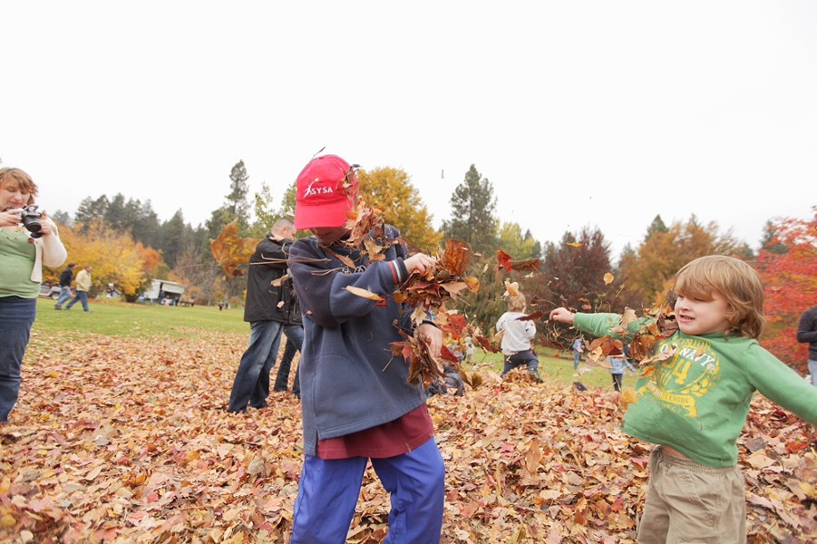 Three-year-old Michael Willis, right, throws leaves at 10-year-old Allen Murray. - YOUNG KWAK