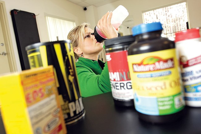 Tracy Carter, owner of Flex Ability Fitness in Spokane Valley, downs some Amino Energy before and during workouts. - YOUNG KWAK