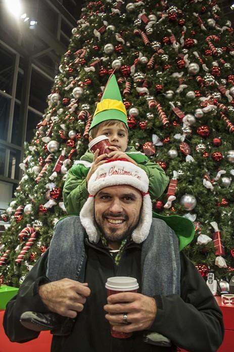 Father Travis Thomas and son Cooper, age 4, wait to see Santa. - SARAH WURTZ