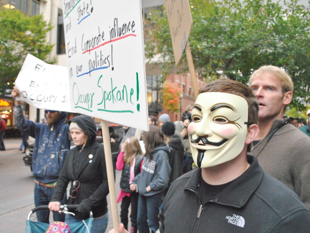 Two marches over the weekend brought hundreds out in the streets, including some sporting Guy Fawkes masks. - CHRIS STEIN