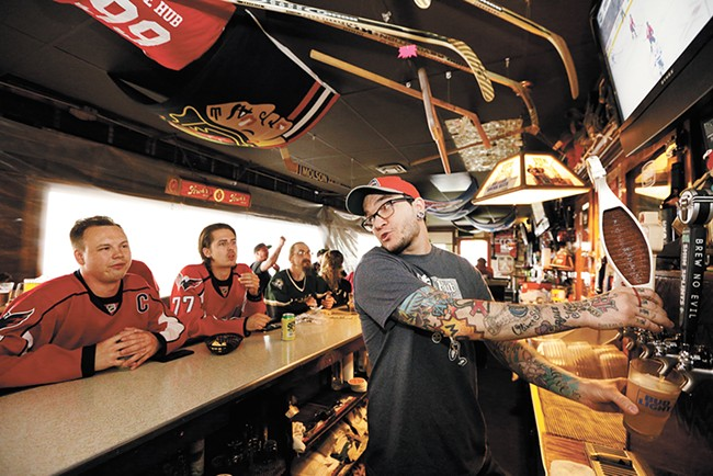 The Hub Tavern co-owner Buddy Richardson pulls a beer for hockey lover Greg Kvasov. - YOUNG KWAK