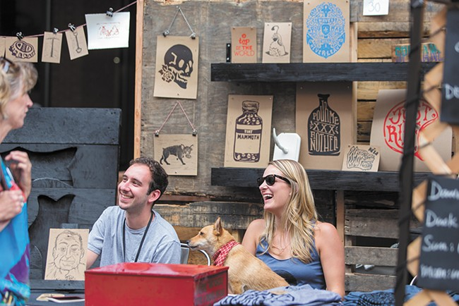 Aaron Abolofia of Tiny Mammoth Ink, left, sits with friend Melissa Estma and dog Lola at 2014's Bazaar, which resulted in about $36,000 in art sales. - MATT WEIGAND