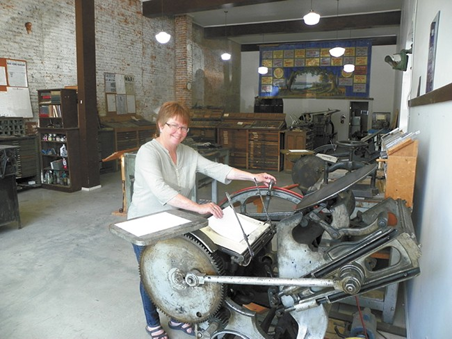 """Palouse native Janet Barstow shows off the """"fingersnapper,"""" an antique printing press. - DAN NAILEN"""