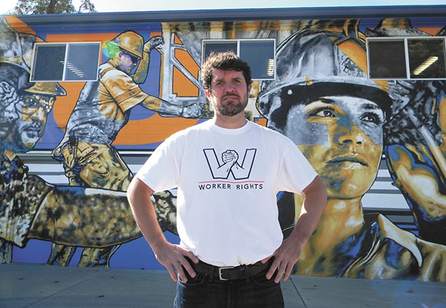 Kai Huschke, the campaign coordinator for Envision Worker Rights, stands next to a labor-themed mural. - JAKE THOMAS