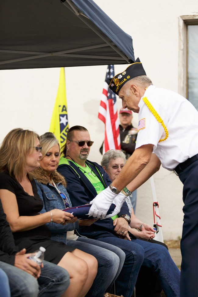 America Legion honor guard member and retired United States Air Force Master Sgt. Harold Mankiewicz, right, hands a flag to Paula Hubeek, left, and Sherry Taylor, second from the left, sisters of Robert Parkinson. - YOUNG KWAK