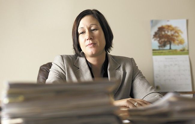 Lisa Chesebro at her desk with massive stacks of legal documents. - YOUNG KWAK