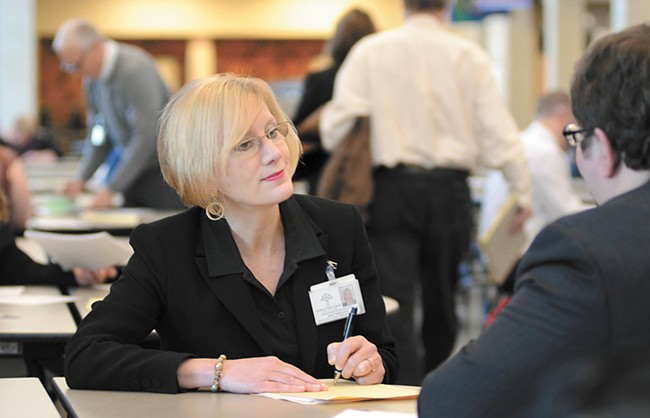 Mary Templeton interviews teaching candidates at a Spokane Public Schools hiring fair last week. - MIKE SALSBURY