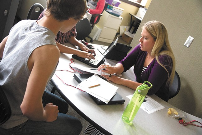 Stephanie Robinette, a special education teacher at Rogers High School, helps students. - JENNIFER DEBARROS