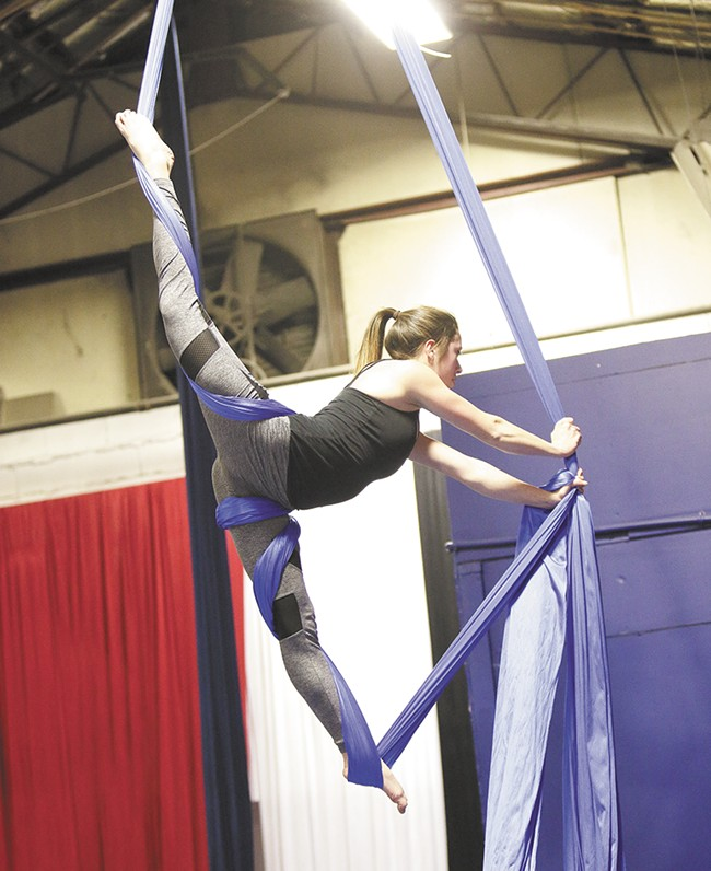 Colorful silks suspend Katie Lynch at Spokane Aerial Performance Arts. - YOUNG KWAK