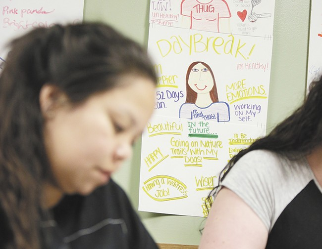 Clients at Daybreak Youth Services concentrate on coloring. In the background is a poster warning of the dangers of meth. - YOUNG KWAK