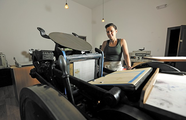Breanna White with her main press, a 1926 machine she restored to working condition two years ago. - YOUNG KWAK