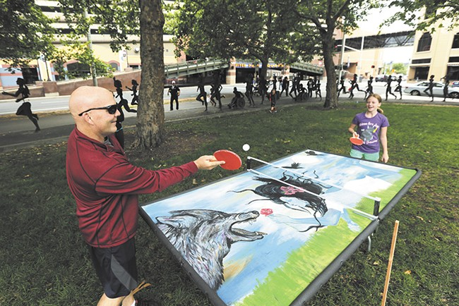 Jeff Moore and his 11-year-old daughter Shelby play ping pong on a mural by Susan Webber at Riverfront Park during a July groundbreaking event for the park's renovation. - YOUNG KWAK
