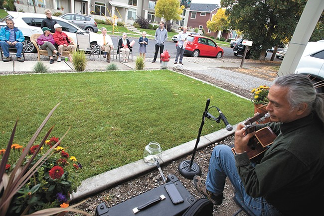 Acoustic guitarist Carlton Oakes plays outside Nick and Michele Follger's West Central home for Porchfest, a music festival aimed at bringing West Central and Kendall Yards together. - NICK FOLLGER
