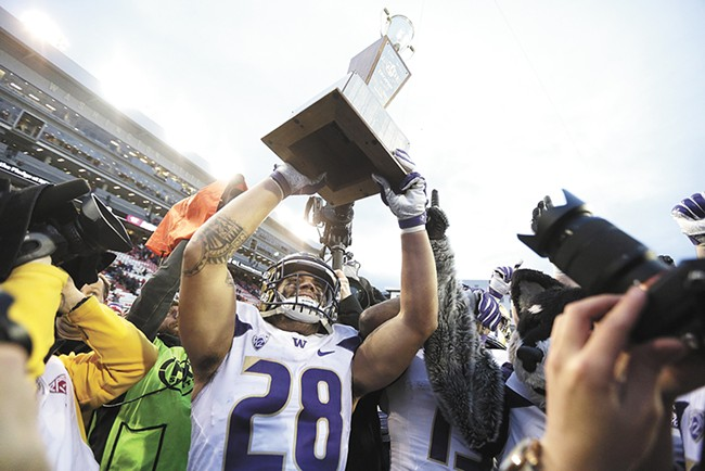 Huskies senior Psalm Wooching holds up the Apple Cup trophy.