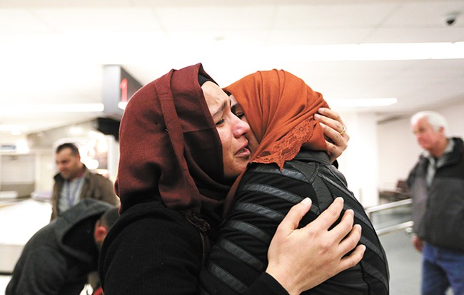 After nearly two years apart, Nadia Amzuabidi (left) hugs her sister, Iraqi refugee Athraa Jameel, tightly as they reunite at the Spokane International Airport Saturday. - YOUNG KWAK