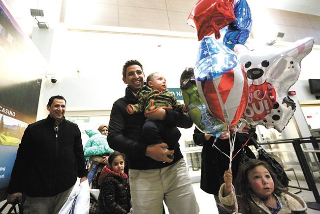 Hamid Nahi (left) smiles as his brother, Assad Al-Sawaedi, holds Nahi's son at Spokane International Airport. - YOUNG KWAK