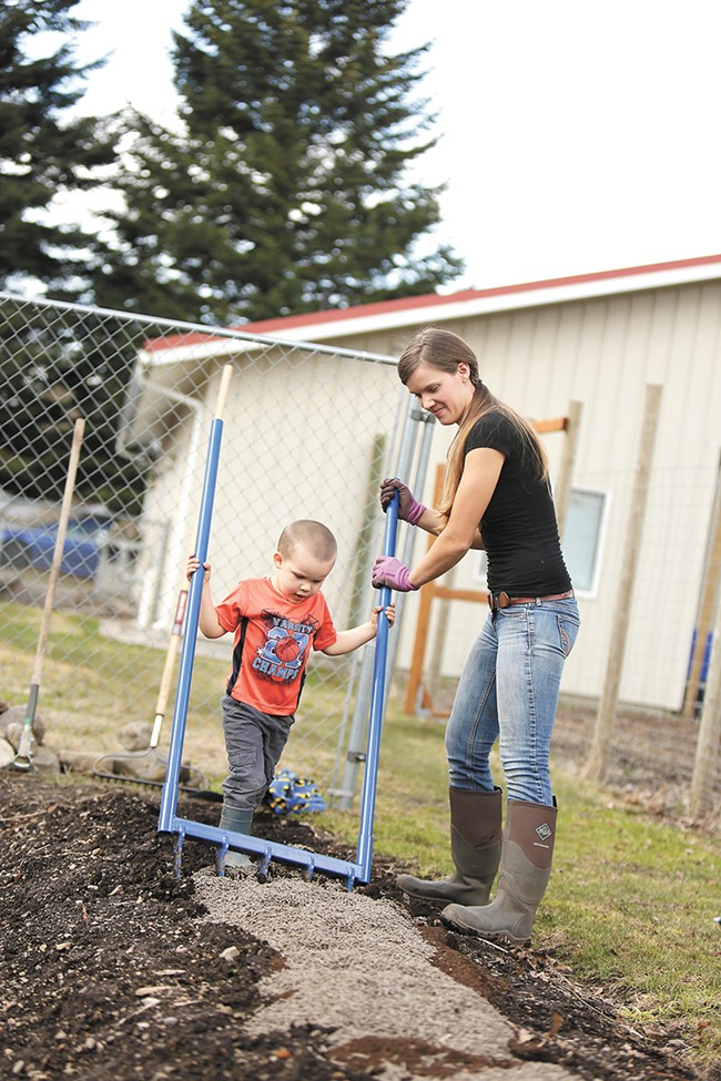 With help from her son, Idaho farmer Erica Gregerson adds organic fertilizer and chicken manure into a garden bed using a broadfork. - YOUNG KWAK