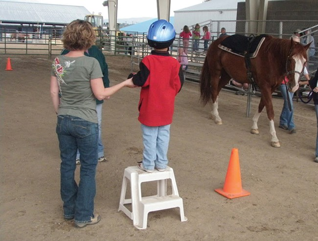 Free Rein volunteer Cyndi Caniglia and a young rider wait for their horse.