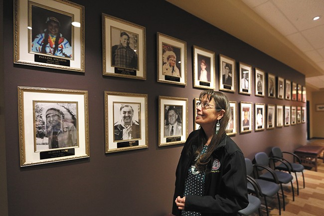 Carol Evans, tribal chairwoman, looks up at a picture of her mother, Pauline Stearns, the first woman to serve on the tribal council. - YOUNG KWAK