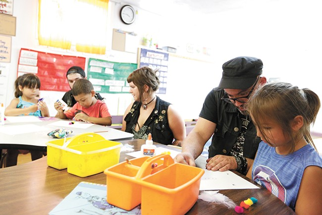 Dan Elliott and 5-year-old Kiaayo (right) work on art projects during a kindergarten class at the Salish School of Spokane. - YOUNG KWAK