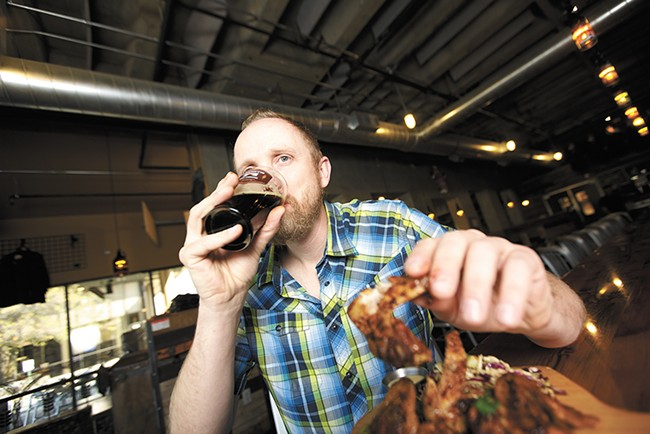 Manito's Patrick McPherson with a Dogfish Head Indian Brown Ale and chicken wings. - YOUNG KWAK