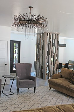 The dazzling living room light fixture was purchased on personal shopping trip to Denver; Lisa designed and crafted the mid-century modern wood screen from scrap lumber on the homebuild site. 