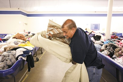 Randy Mora folds a blanket he wants to buy at the Goodwill Outlet Store. - YOUNG KWAK