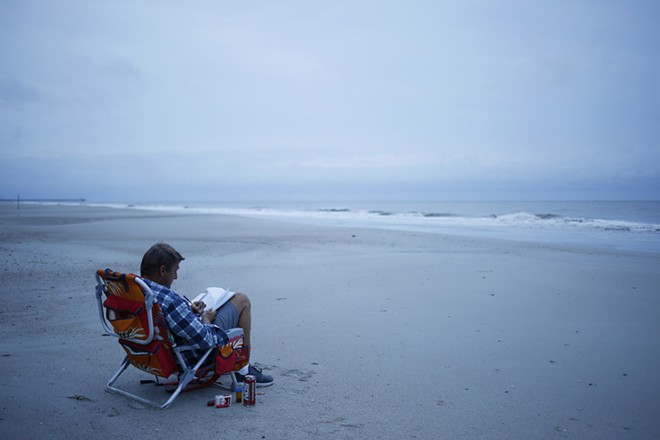 Jerry Bryant spends time on the beach before the arrival of Hurricane Florence in Myrtle Beach, S.C., Sept. 13, 2018. The first rains of Florence were starting to lash North Carolina on Thursday, with the storm growing in size, packing winds of up to 110 miles an hour and driving a storm surge that could reach 13 feet in places. - LUKE SHARRETT/THE NEW YORK TIMES