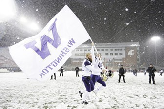 Washington punter Joel Whitford and long snapper A.J. Carty carry the school flag after their team defeated Washington State 28-15 on Nov. 23. - YOUNG KWAK