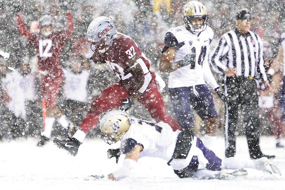 """GETTING SNOWED"" - Washington State running back James Williams runs over Washington defensive back Taylor Rapp during the first half of the Apple Cup in Pullman Nov. 23. UW won 28 to 15."