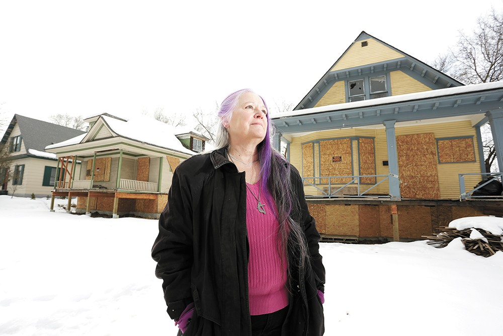 Deb Conklin stands in front of boarded-up homes she hopes to convert into affordable housing. - YOUNG KWAK PHOTO