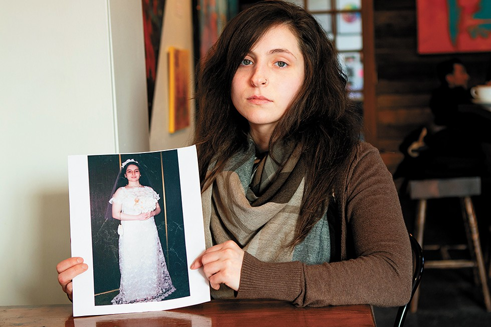 Angel McGehee, née Dwyer, holds a photo from her wedding day, when she was just 13. - JEFF FERGUSON PHOTO