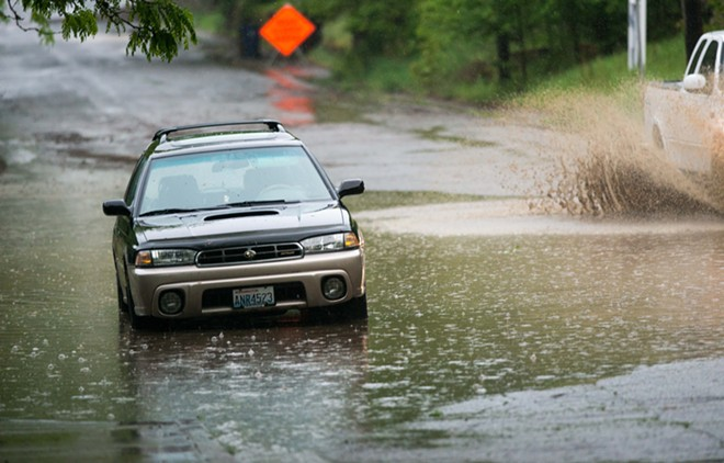 A car sits parked in a massive puddle in flooded Peaceful Valley during last night's rainstorm. - DANIEL WALTERS PHOTO