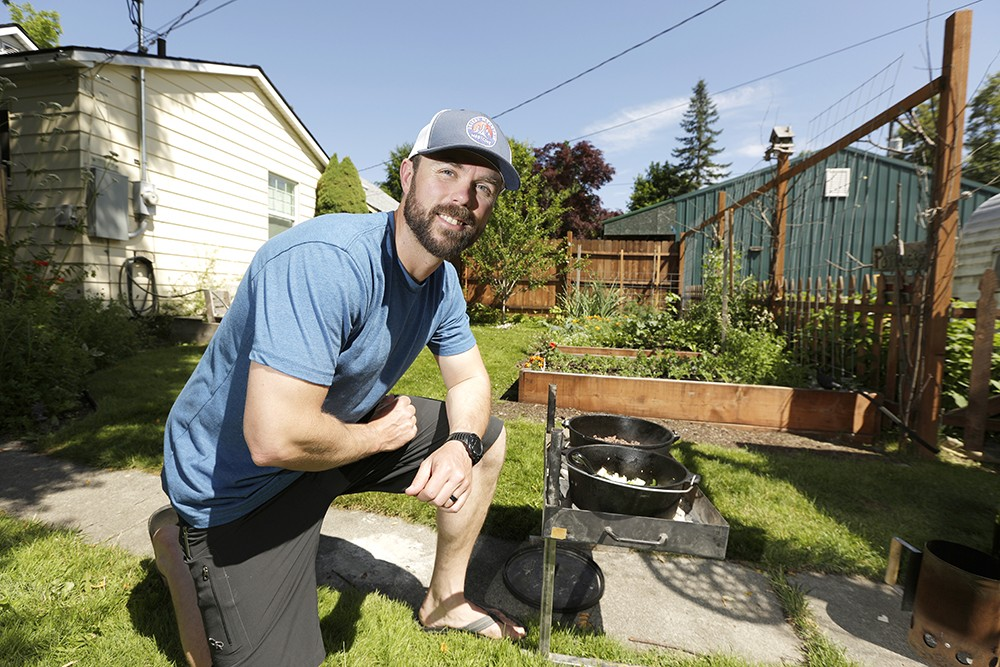 Jacob Rothrock, who teaches outdoor living skills at North Idaho College, fires up the grill for a Dutch oven cooking tutorial in his back yard. - YOUNG KWAK PHOTO