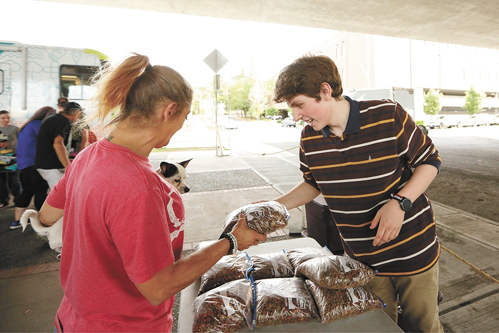 Avery Plank, 16, passes out pet food to owners in need. - YOUNG KWAK