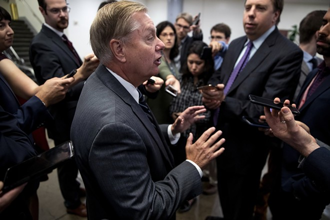 Sen. Lindsey Graham (R-S.C.) talks to reporters in the Capitol before the weekly Senate policy luncheons in Washington on Tuesday, Oct. 22, 2019. Graham, a fierce defender of the president, planned to introduce a resolution condemning the impeachment inquiry being led by Democrats. - ANNA MONEYMAKER/THE NEW YORK TIMES