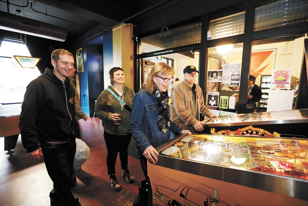 Debbie Tansy plays the Taxi pinball machine as her husband, Ray Tansy, right, David Strom, left, and Kacie Strom look on at Berserk.|young kwak photo - YOUNG KWAK PHOTO