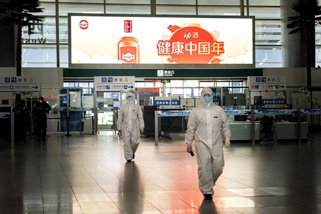 People, wearing protective clothing to guard against the coronavirus, walk in the departure hall of the Beijing South railway station in Beijing on Monday, Feb. 10, 2020. - GIULIA MARCHI/THE NEW YORK TIMES