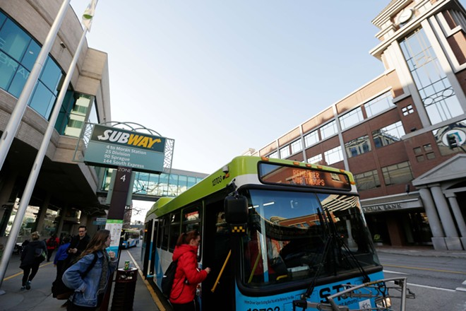 Riders board an STA southbound route 4 bus at the STA Plaza. - YOUNG KWAK PHOTO